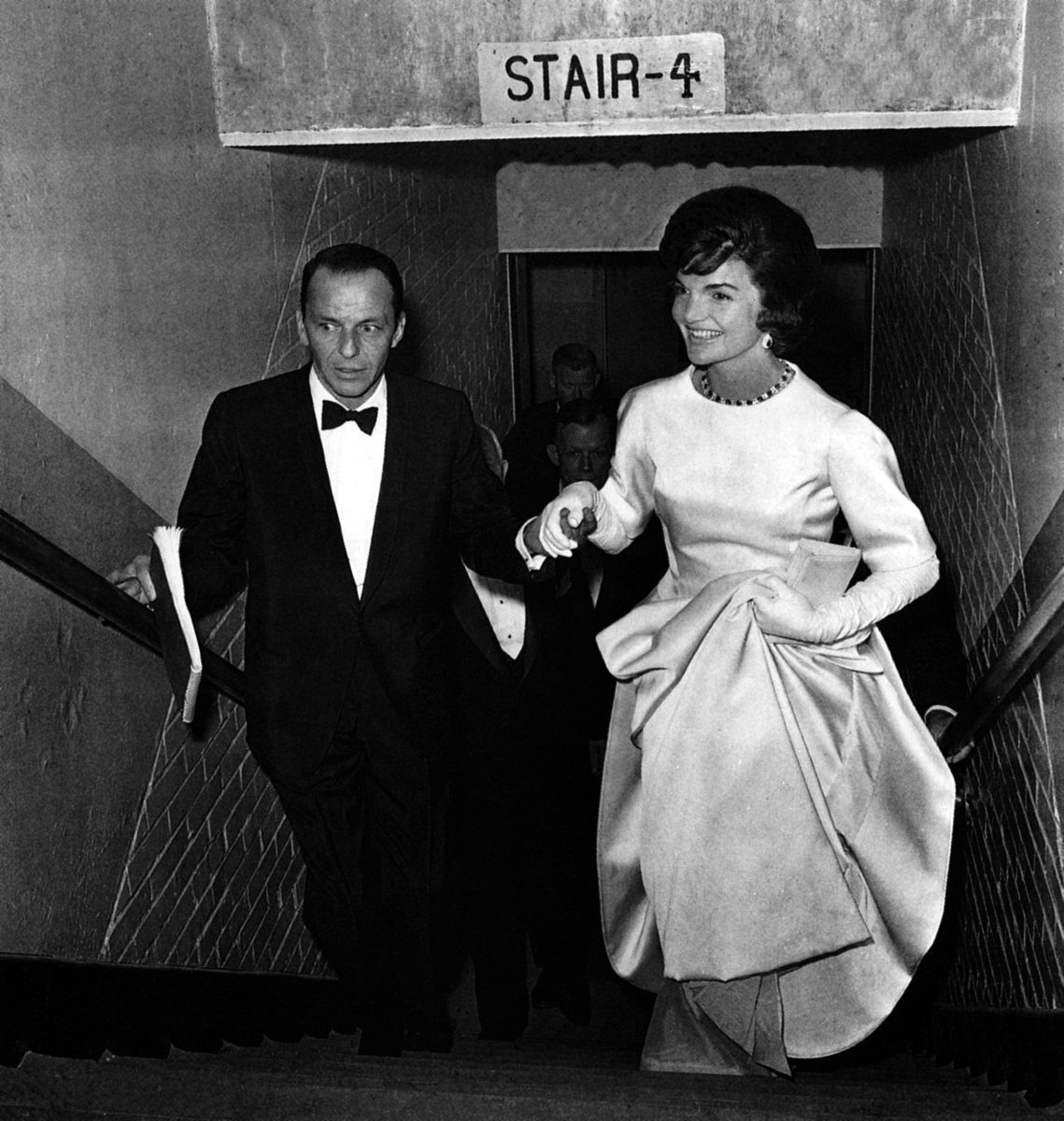 Frank Sinatra escorts Jacqueline Kennedy up the stairs during the inaugural gala at the National Guard Armory in Washington, D.C. on January 19, 1961