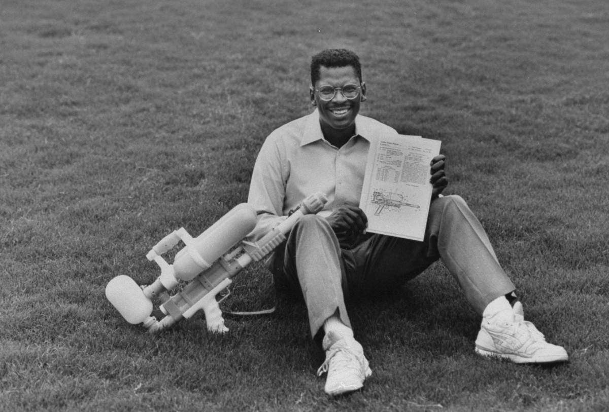 Lonnie Johnson holding a Super Soaker and its U.S. patent while sitting on the grass outside his home, June 1992