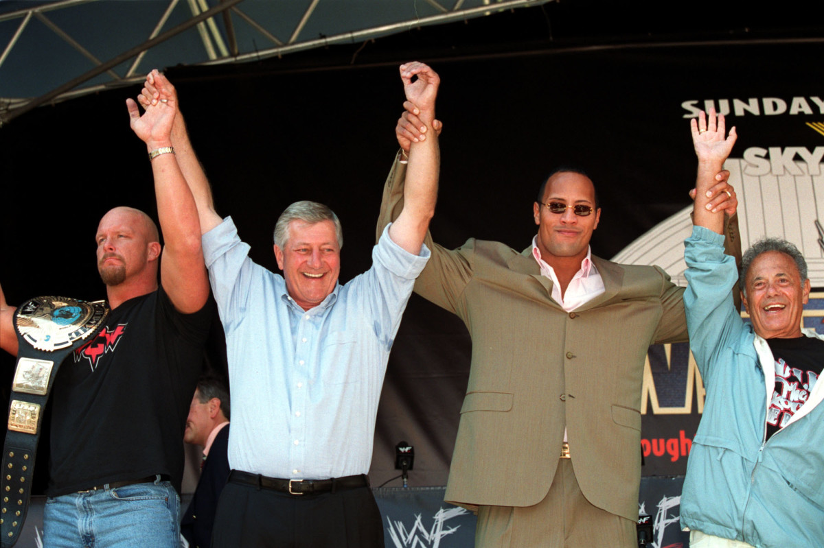 """(L-R) """"Stone Cold"""" Steve Austin, Ontario Premier Mike Harris, Dwayne """"The Rock"""" Johnson and Toronto mayor Mel Lastman raise their hands at Nathan Philips Square after it was announced that WestleMania 18 will take place at the Skydome on March 17, 2001"""