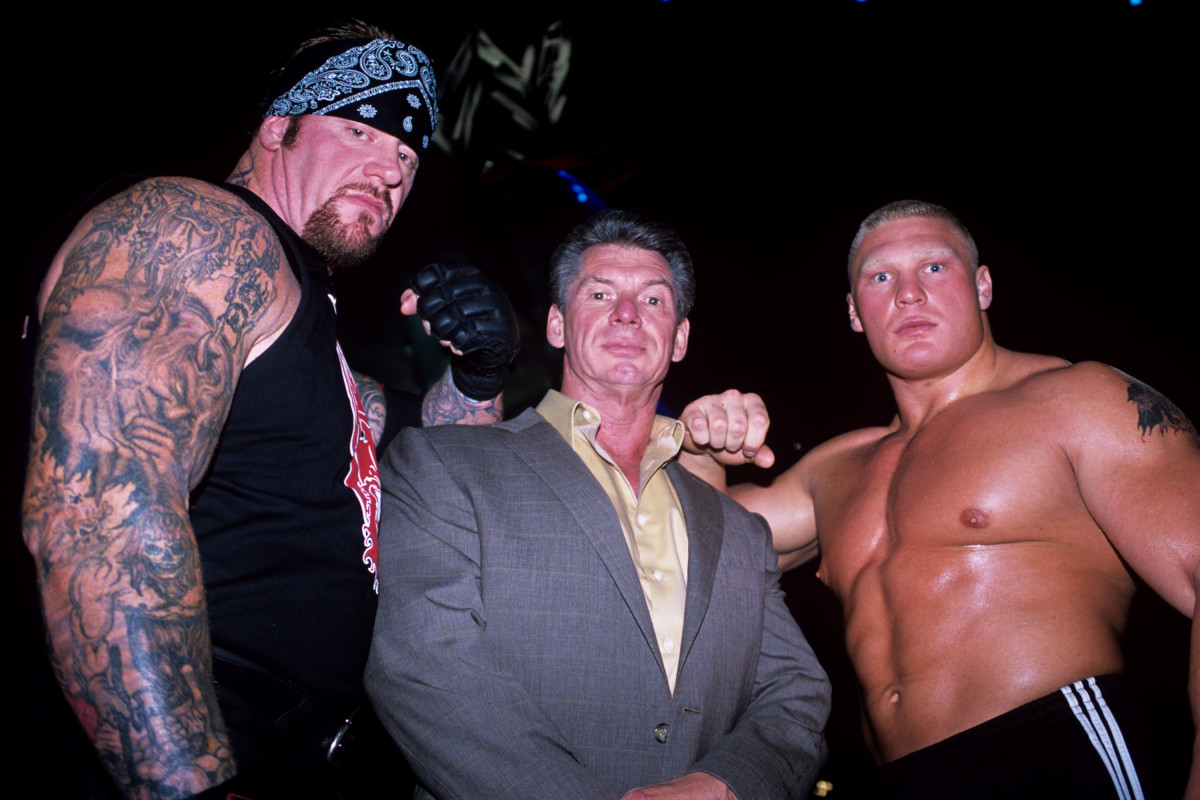 Vince McMahon (C) flanked by WWE superstars The Undertaker (L) and Brock Lesnar (R)