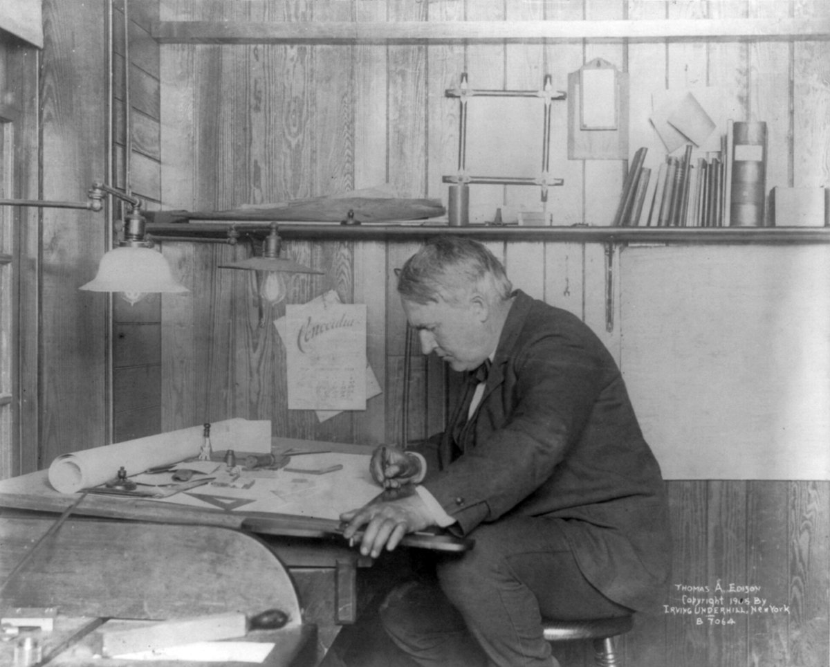 Thomas Edison seated at his desk writing in 1905