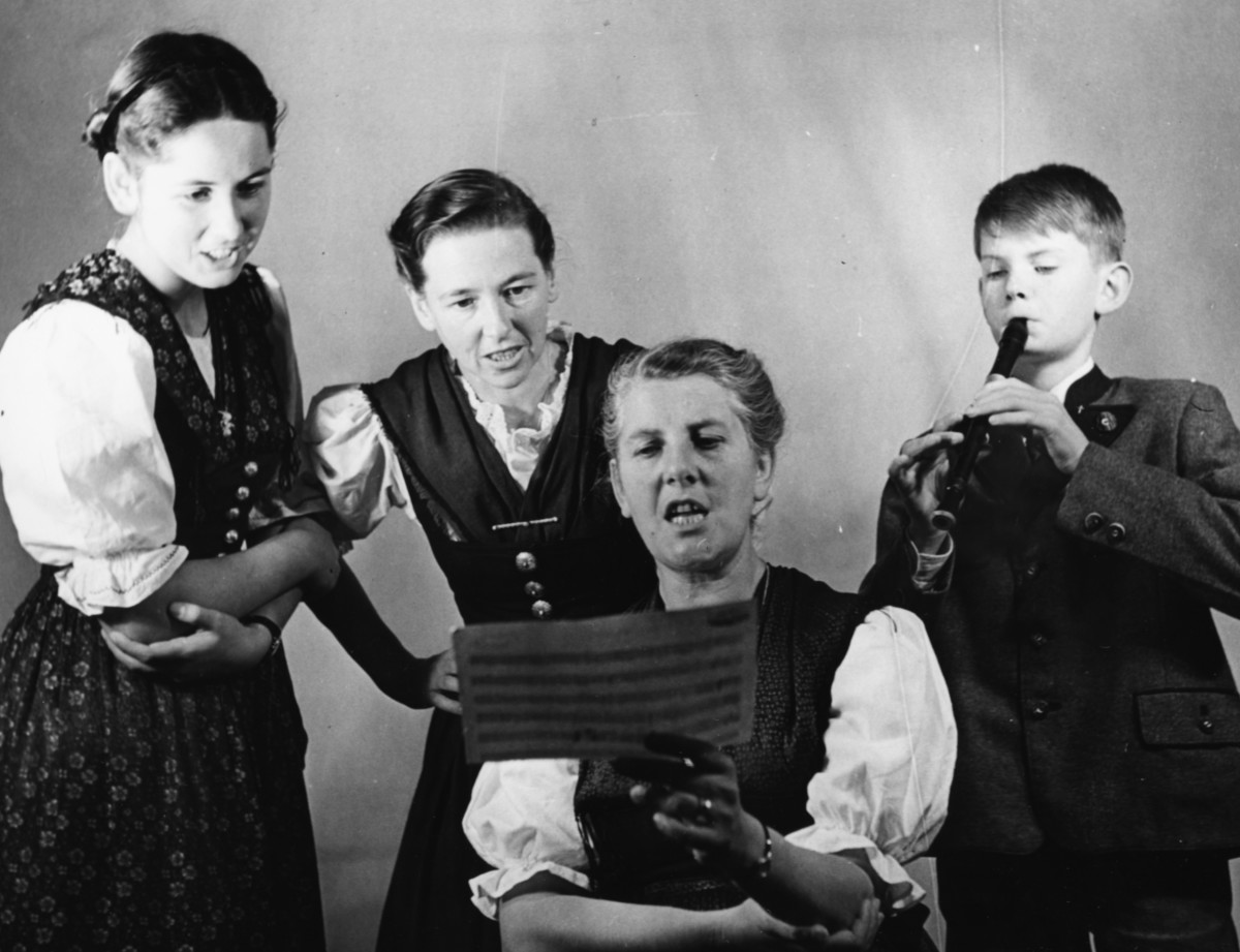 Maria Von Trapp and three of her children, (L-R) Eleonore, Agatha and Johannes, singing from a piece of sheet music, London, circa 1950.