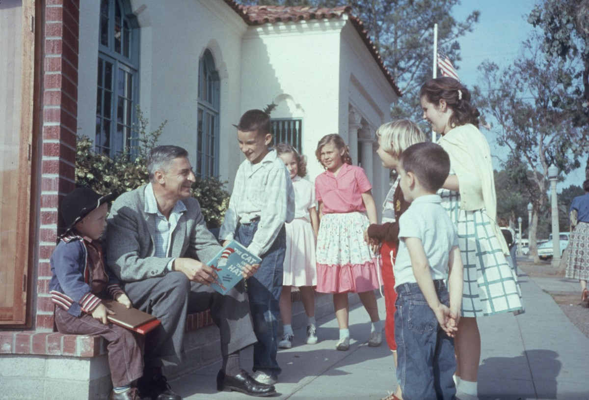 Dr. Seuss talking with a group of children while holding a copy of 'The Cat in the Hat' in La Jolla, California, on April 25, 1957