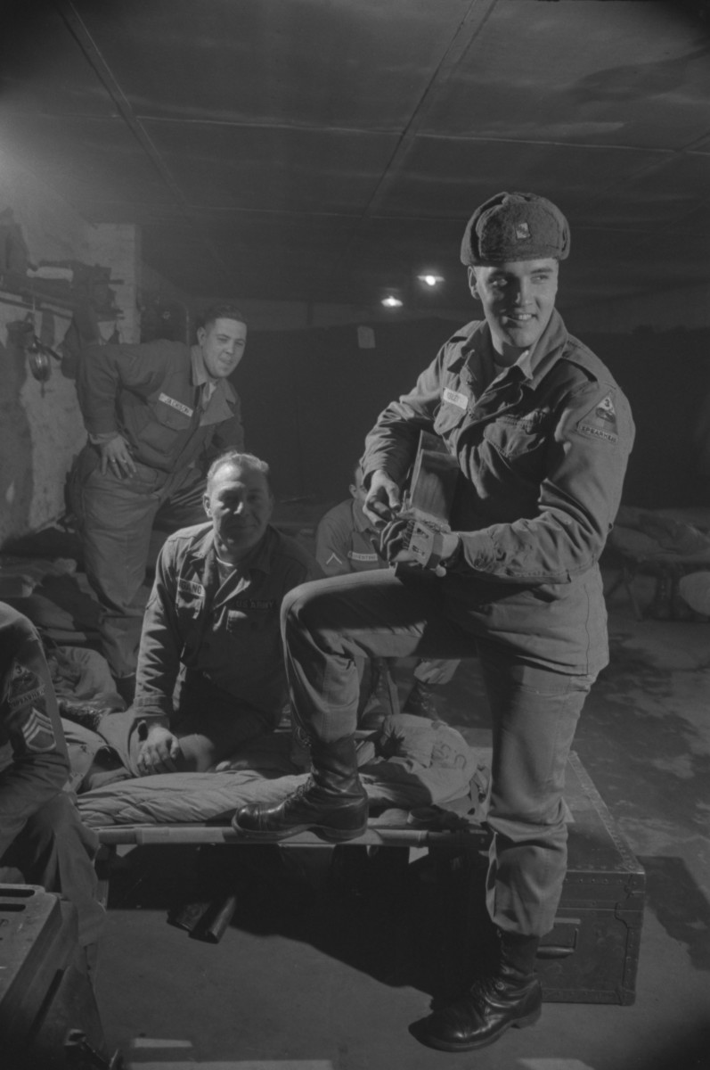 Elvis Presley playing acoustic guitar for fellow soldiers in a military barrack near the end of his service in Bad Nauheim, Germany, March 1960