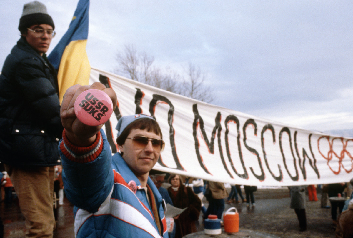 American protesters at the Lake Placid Games opening ceremony hold various signs of protest against the Russians including a sign fostering boycott of the 1980 Moscow Summer Olympic Games.
