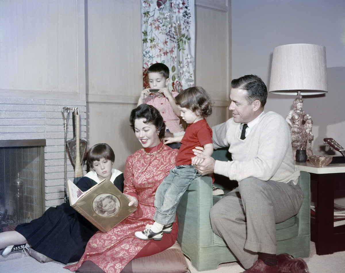 Shirley Temple (center) at home with her family in 1957: (clockwise from bottom left) daughter Susan Agar, son Charles Black Jr., daughter Lori Black and husband Charles A. Black