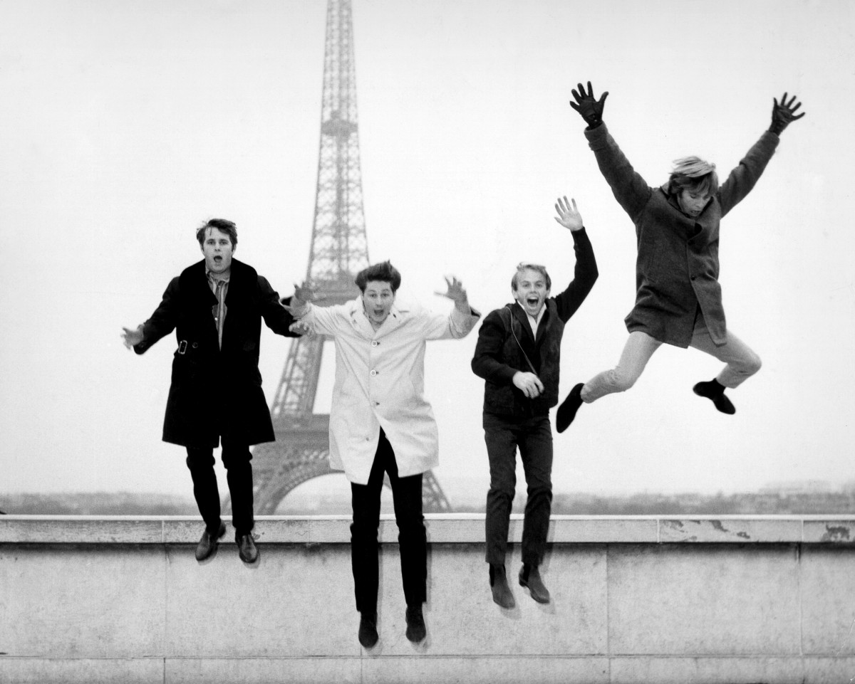 The Beach Boys jump off a ledge in front of the Eiffel Tower in November 1964 in Paris, France.