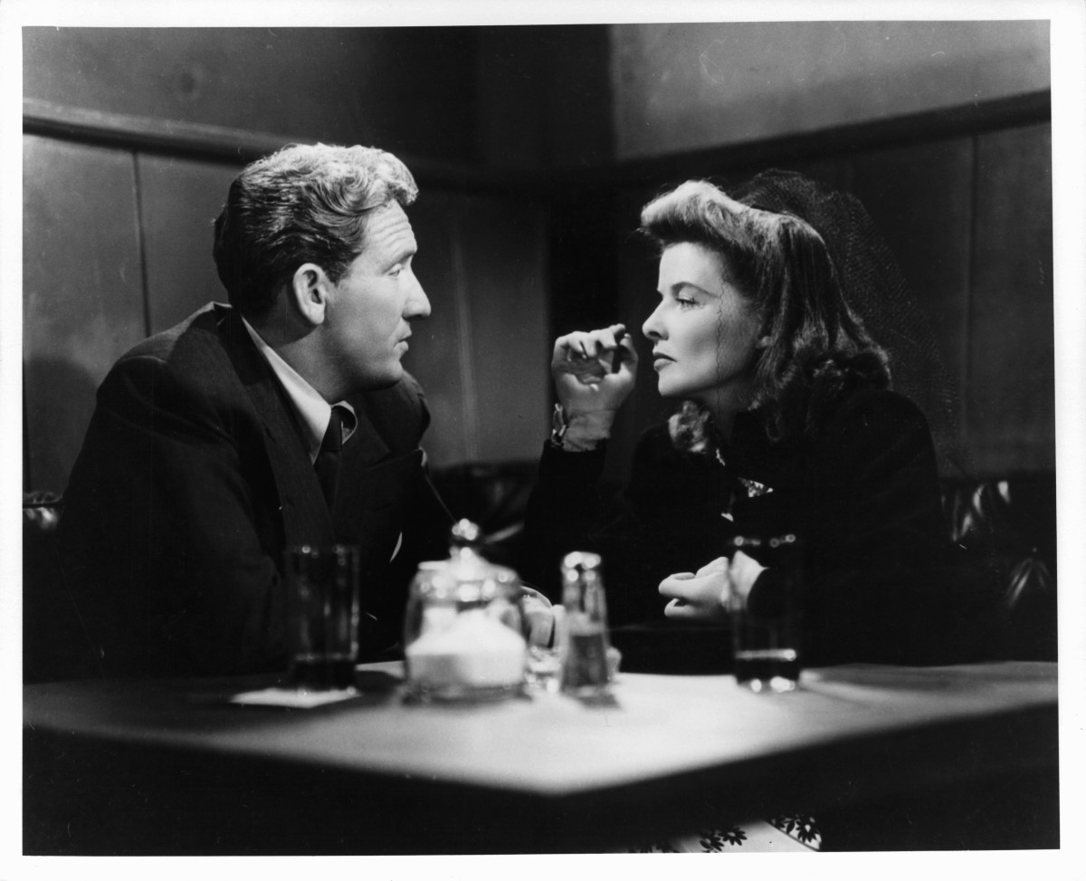 Spencer Tracy and Katharine Hepburn having drinks together at small table in a scene from the film 'Woman Of The Year'