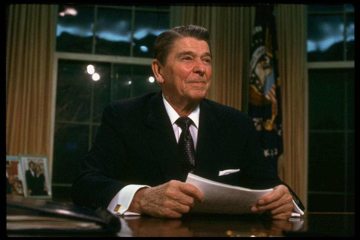 Ronald Reagan sitting at desk in the Oval Office of the White House after addressing the nation, re Iran-Contra affair.